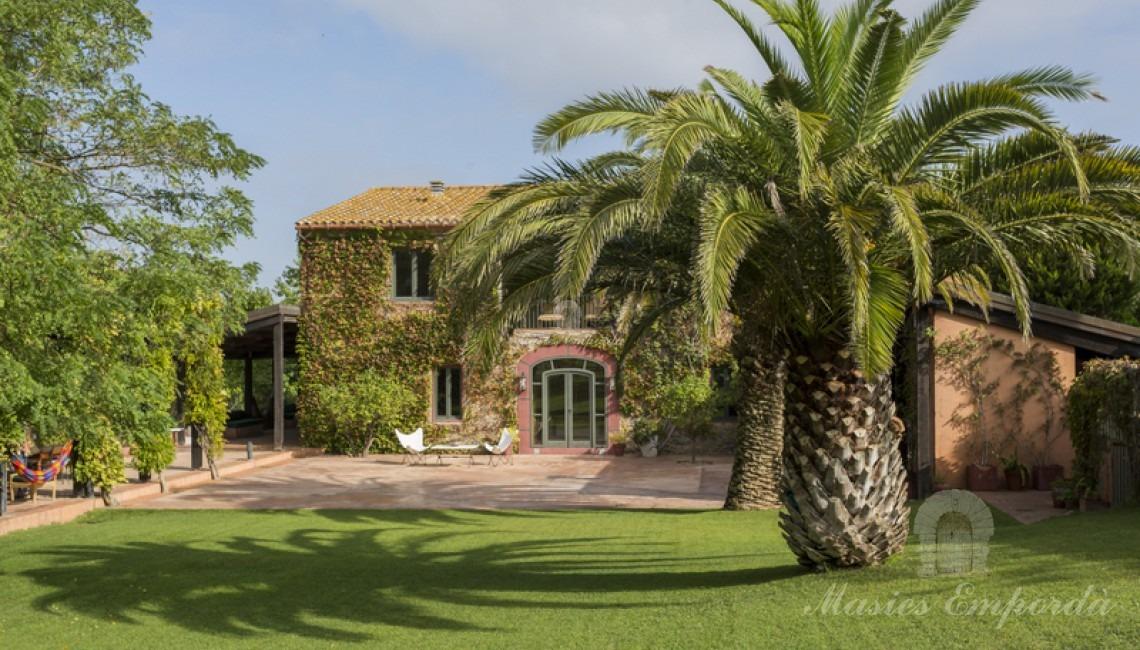 Vista fachada sur de la Masía con verde y exuberante yedra trepadora que cubre la totalidad de ella
