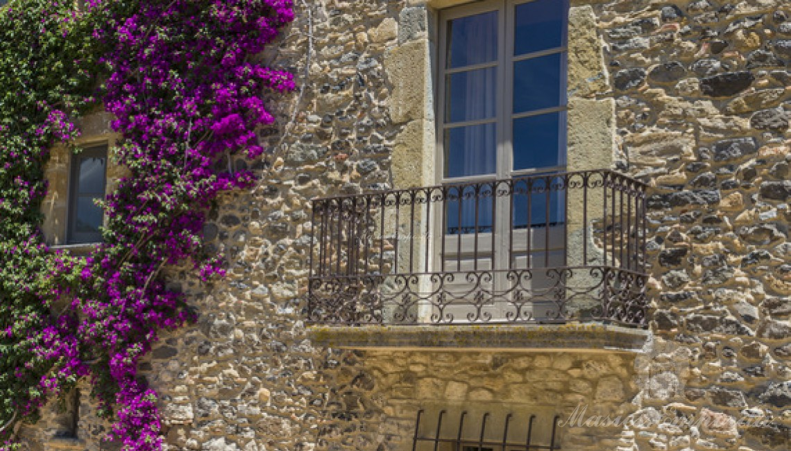 Parte de la fachada lateral de la masía con balcón en forja