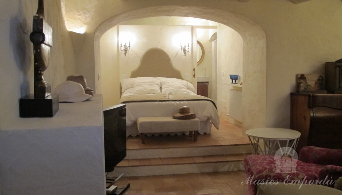 Habitación suite con baño con acceso en el lateral de la pared cabecera de la cama, con arco de medio punto que la separa del salón de estar en primer plano con vigas vistas de madera en cubierta