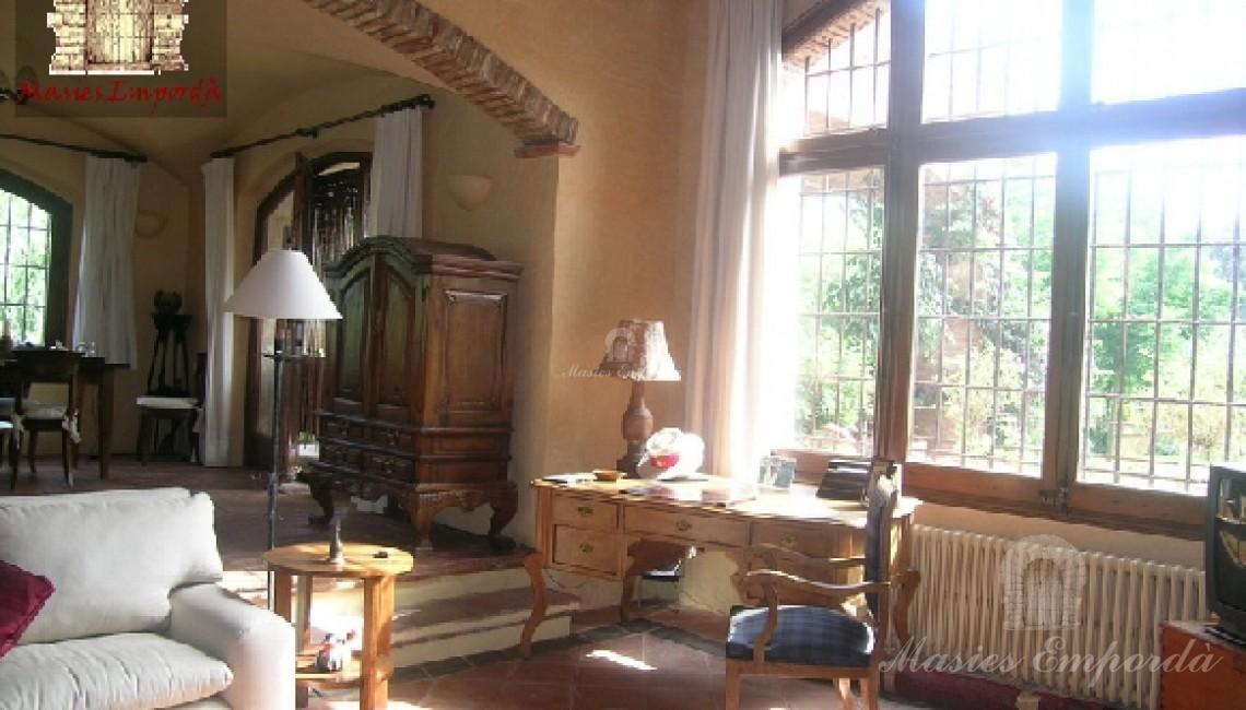 Salón comedor principal de la casa a dos niveles de altura y de pavimento con chimenea y vistas el jardín, piscina y porche con barbacoa