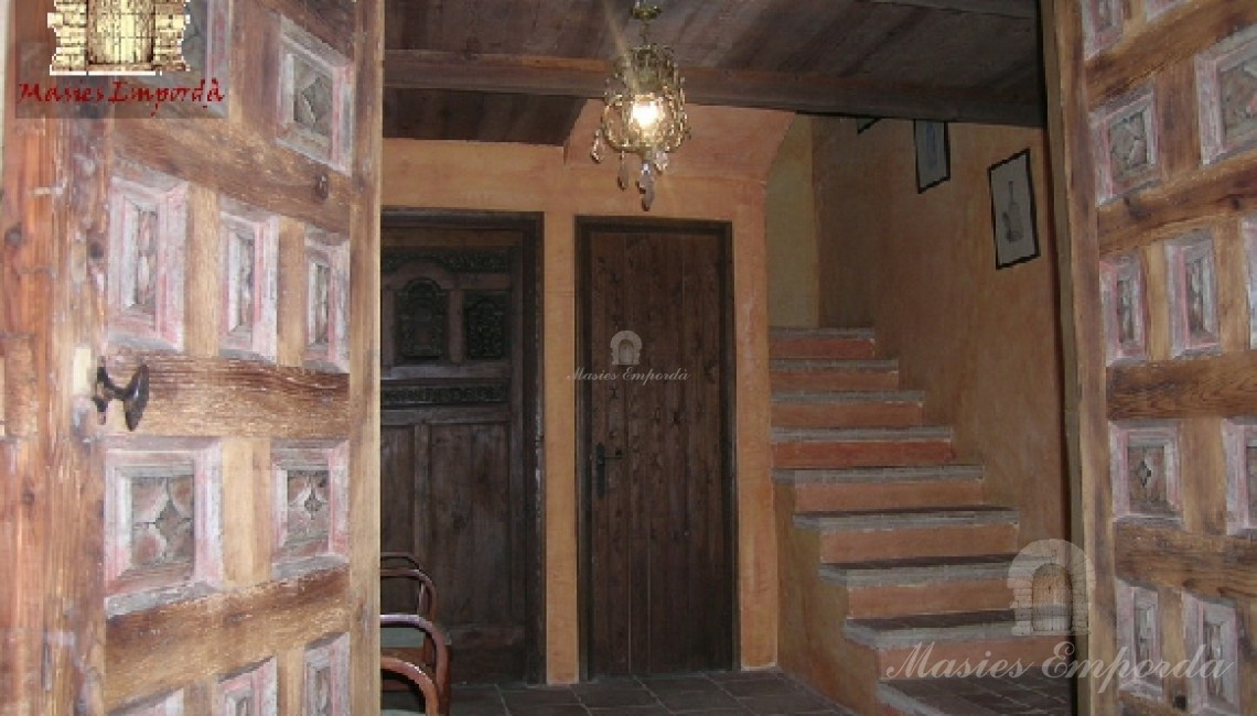 Hall distribuidor de planta baja de la casa con vista de la escalera de acceso y varias habitaciones