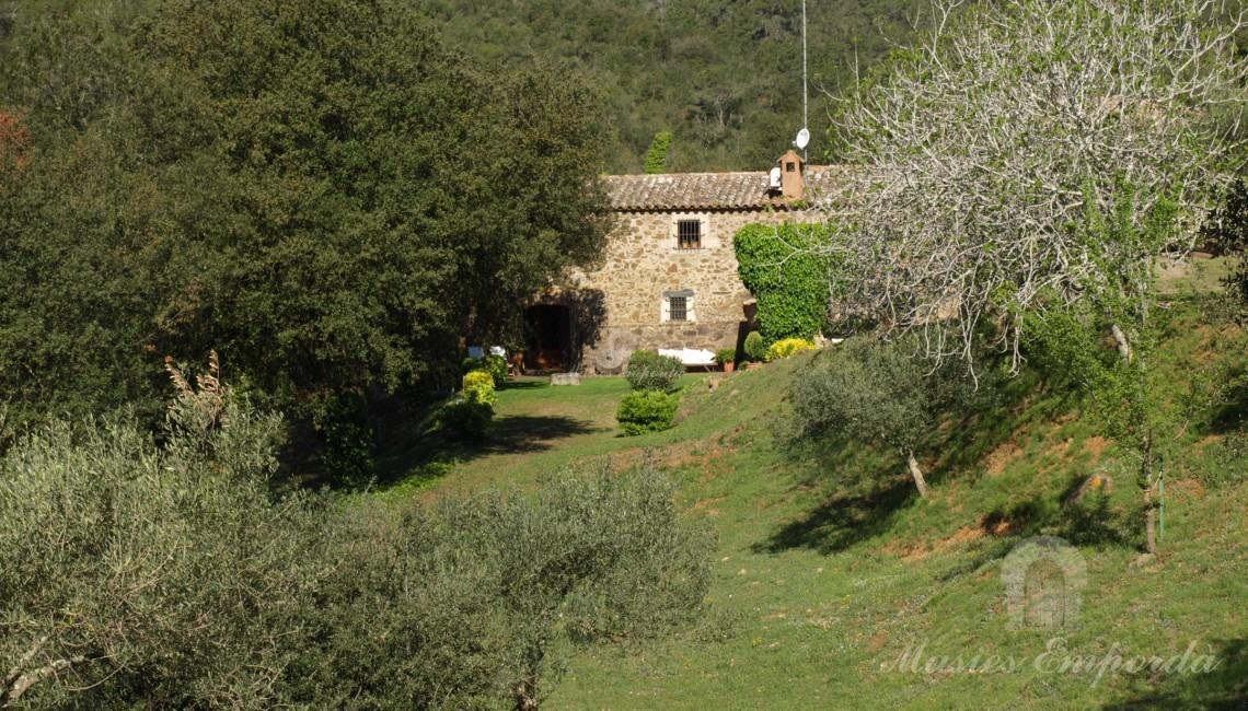 Vista del terreno y fachada principal de la masia