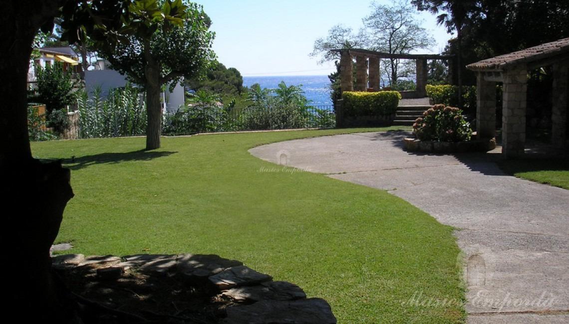 Paseo pavimentado del jardín hacia glorieta con vistas a la playa de Fornell.