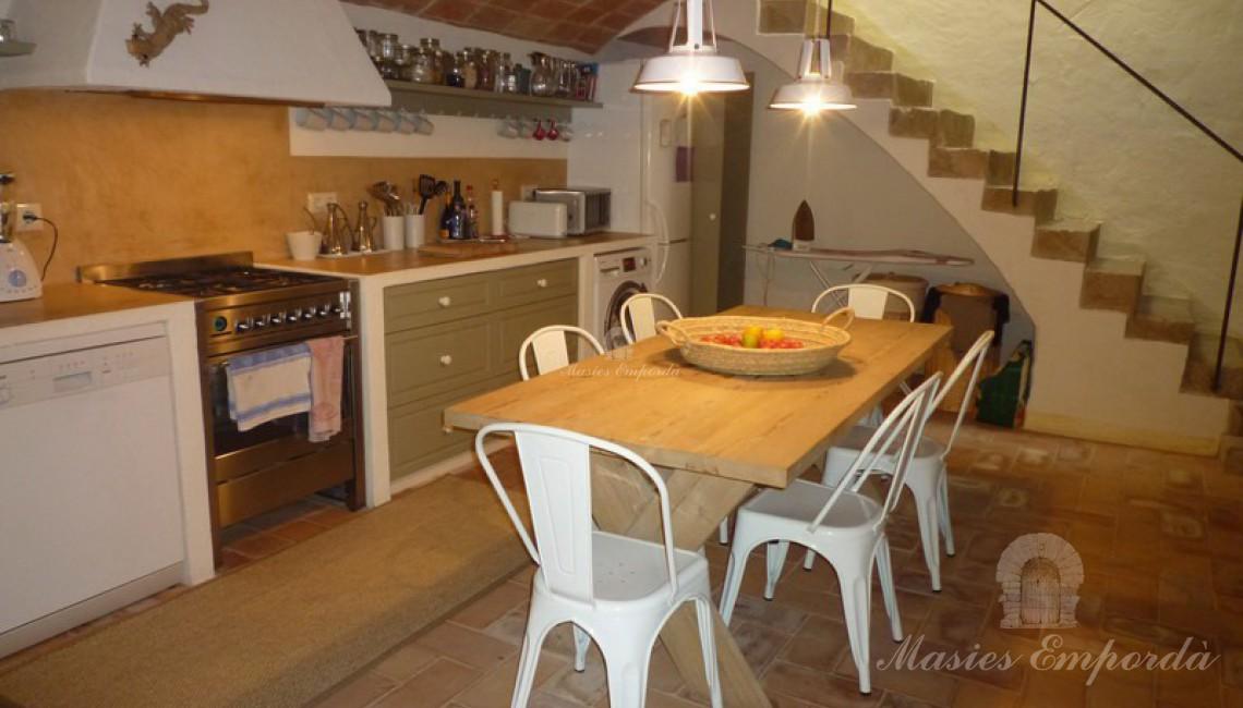 Cocina abovedada espaciosa completamente equipada con mesa de desayunos en el centro desde donde se aprecia la escalera de acceso a planta