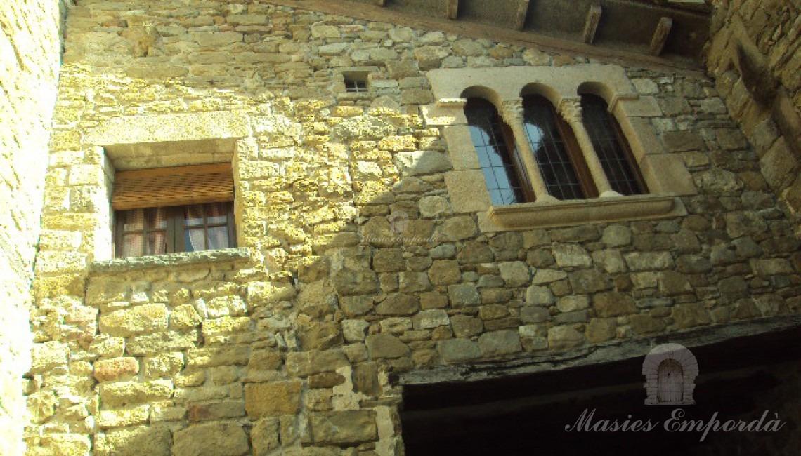 Detalle del patio interior del castillo donde se aprecia los ventanales que dan al salón principal del castillo y alcobas