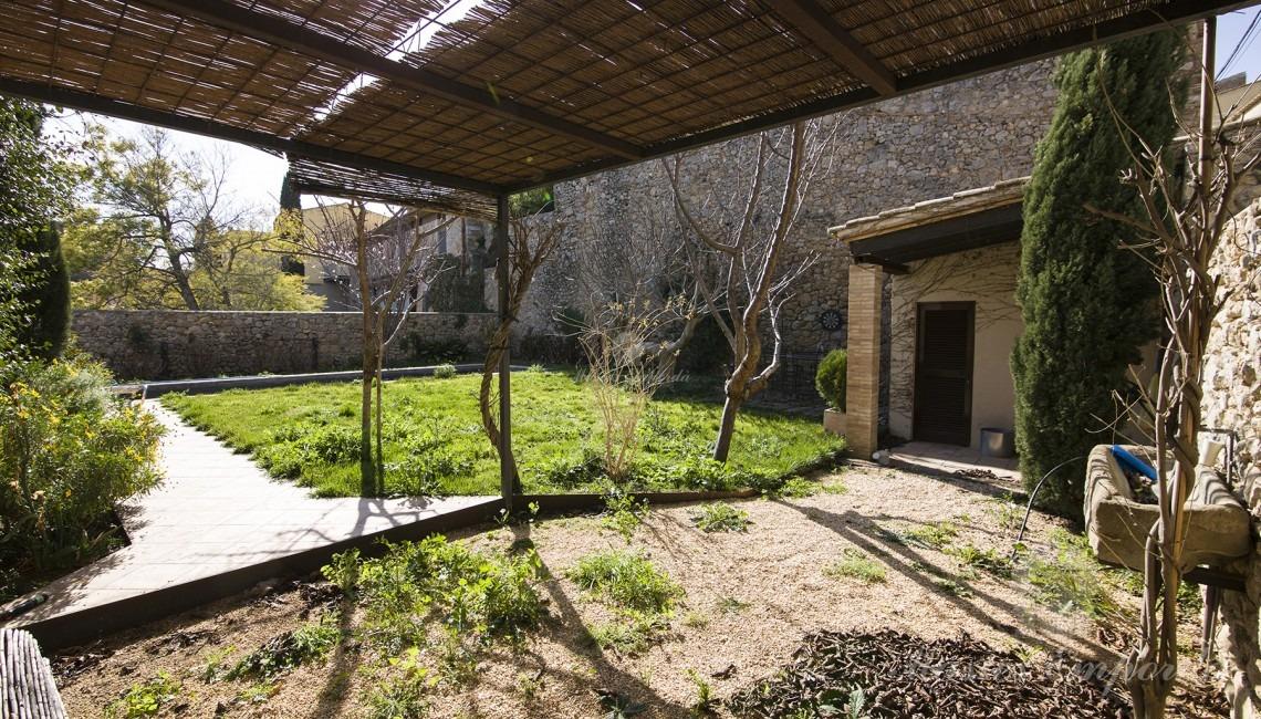 Vista de la piscina y la terraza con el porche de la casa