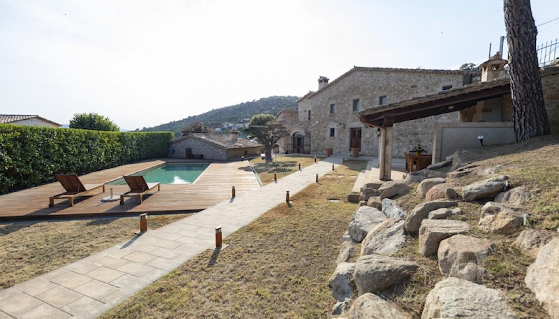 Fachada de la masía y vistas del jardín y piscina