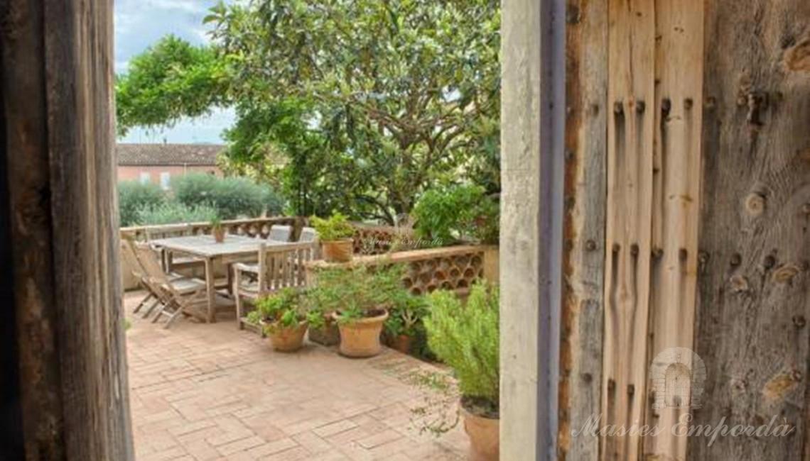 Vista de la terraza y del jardín con árbol de un verde intenso con mesa de madera con la puerta de madera con remaches de clavos de forja