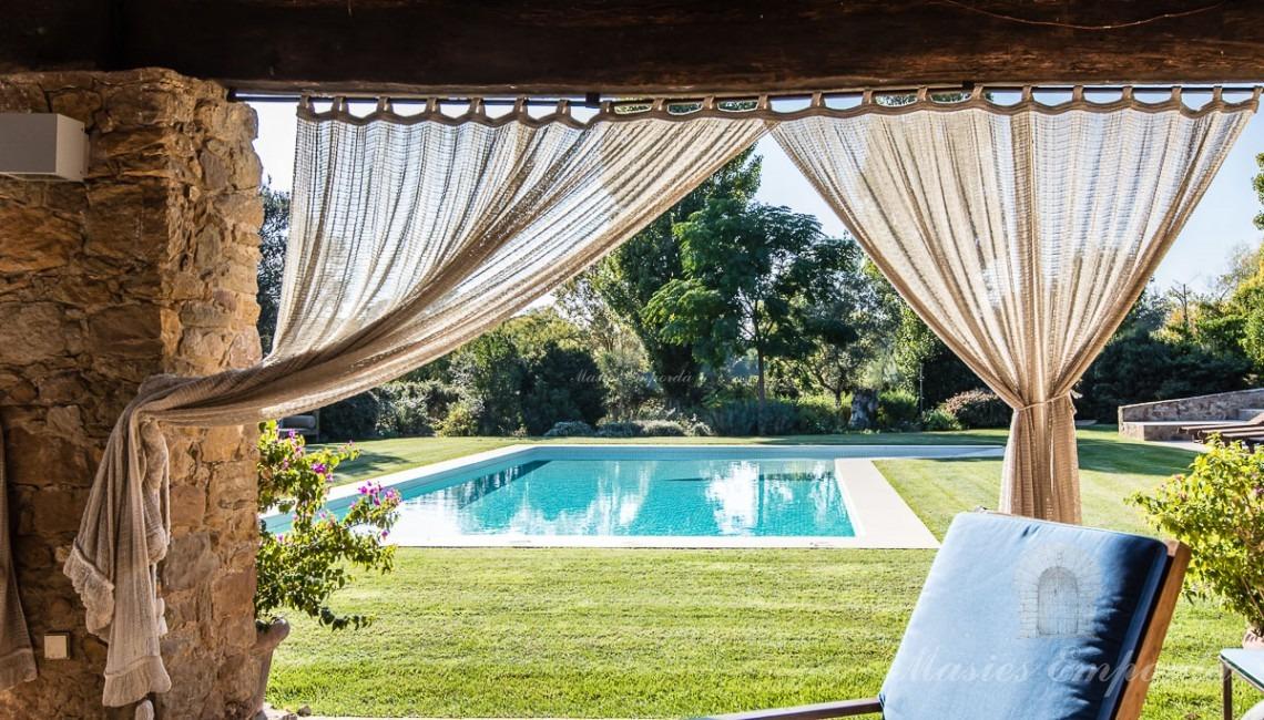 Desde otro ángulo vista desde el porche hacia la piscina y el jardín