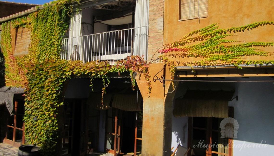 Fachada posterior de la casa con porche y terraza en la segunda planta