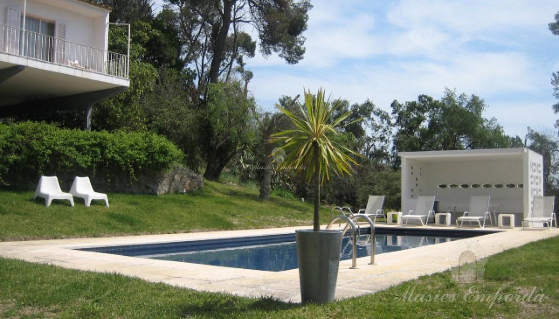 Detalle de la zona de la piscina con pequeño porche en blanco que contrata con el verde del maravilloso jardín de la propiedad
