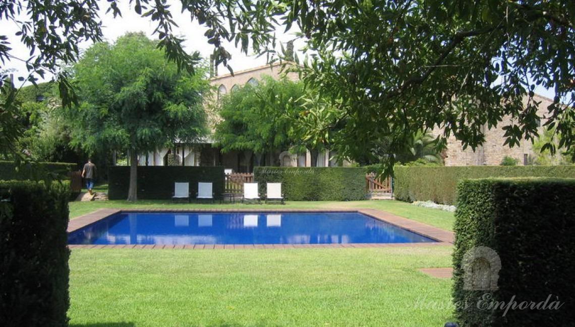 Vista desde el jardín de la piscina y de la casa al fondo de la imagen