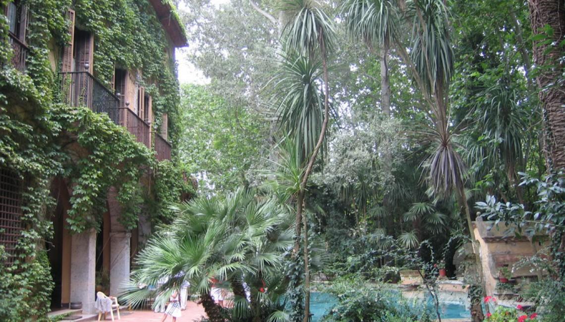 Detalle de la fachada principal de la casa completamente cubierta de yedra trepadora con la piscina en un lateral de la imagen