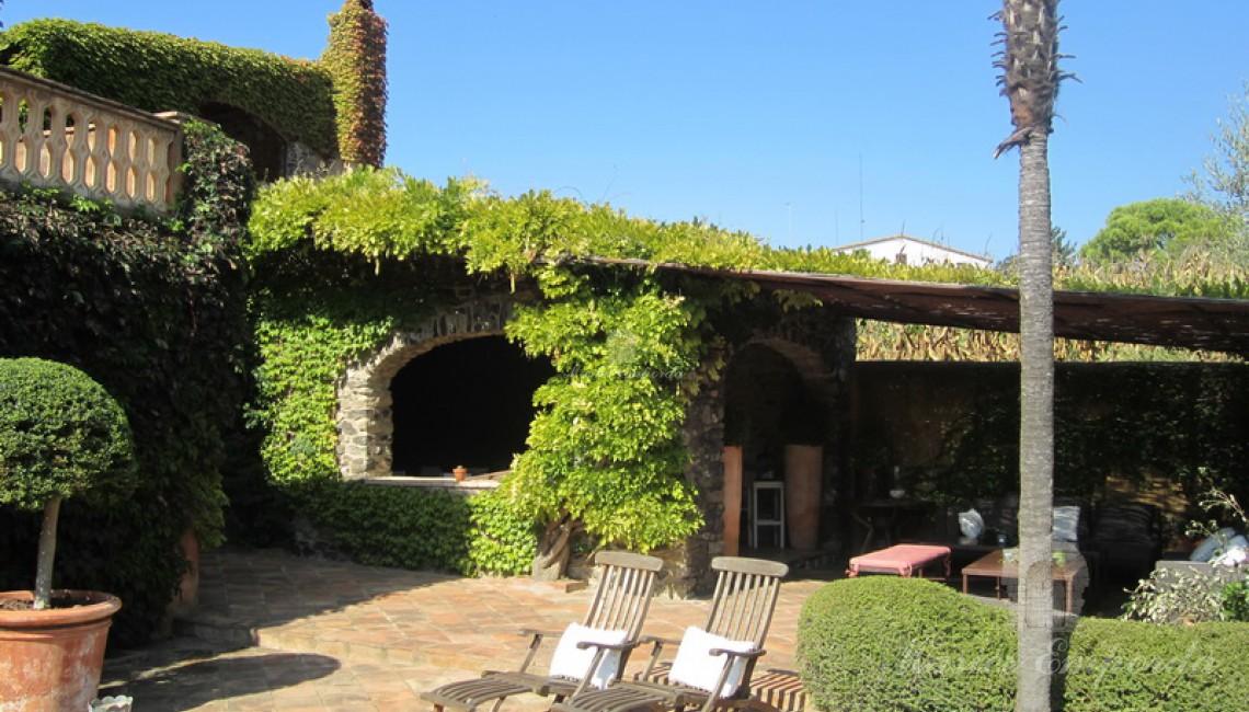Detalle del porche adjunto a la casa conde se encuentra un comedor de verano y una barbacoa así como salón de estar exterior cubierta.