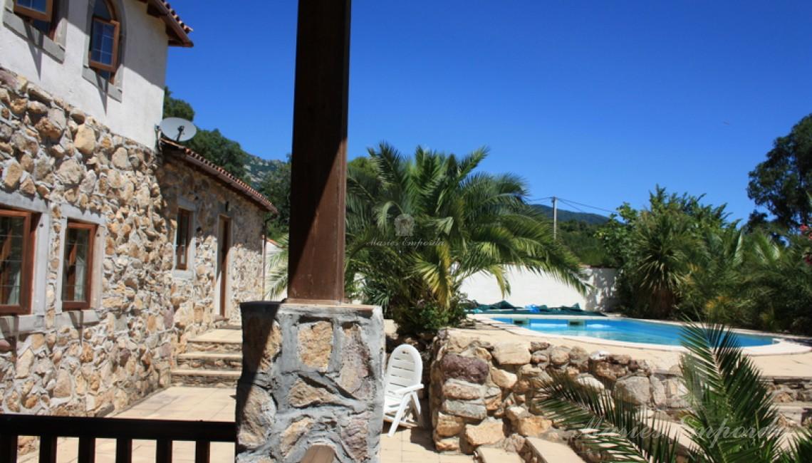 Vista de la piscina desde la terraza cubierta de la casa con vistas al valle