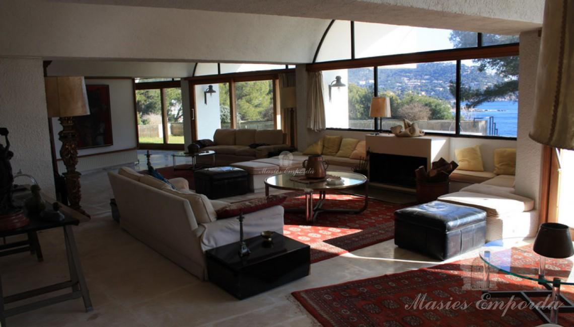 Vista del salón con chimenea con vistas al jardín y al mar.