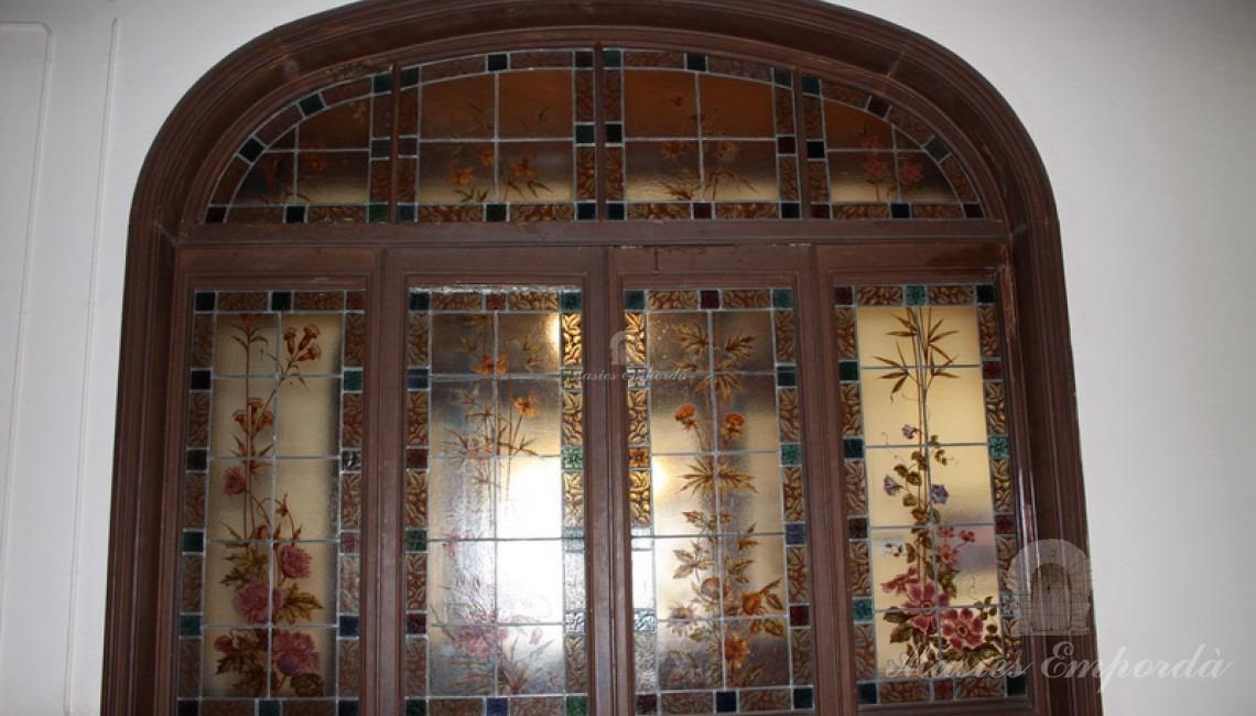 Puerta de acceso a planta también en madera y acristalamientos con dibujos con motivos florales