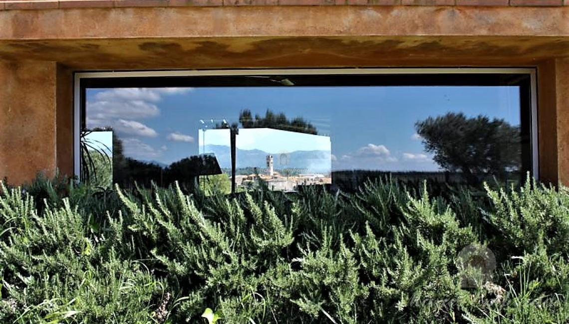 Detalle de los ventanales simétricos del salón con vistas a través de ellos del pueblo.