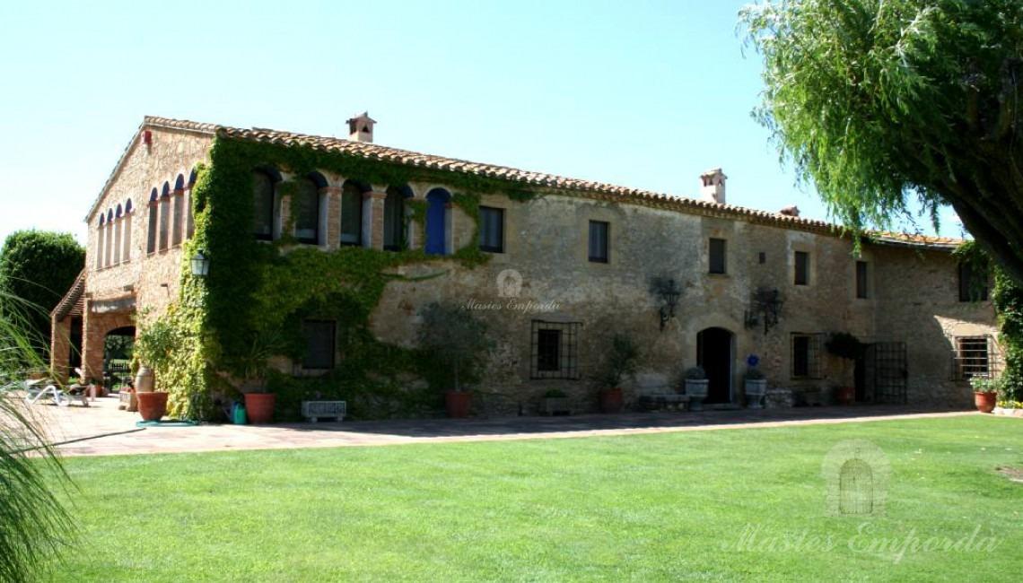 Vista lateral de la masía y los porches anexo a ella rodeada del gran jardín y al fondo la antigua torre de defensa la propiedad que está ubicada Regencos Baix Empordà