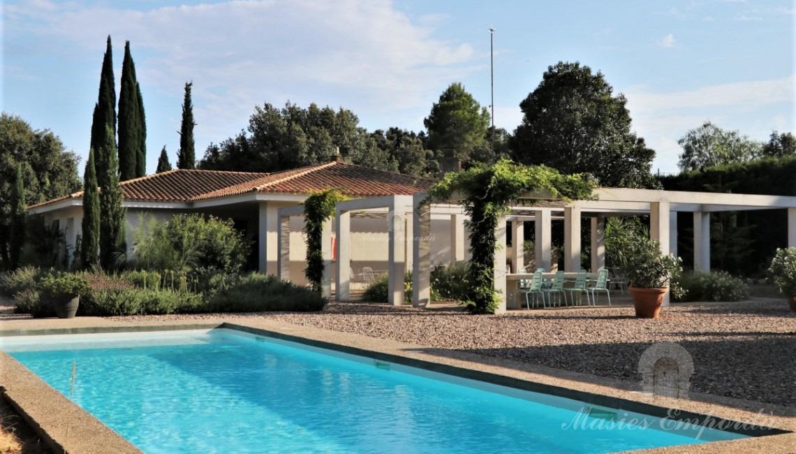 Vista general de la casa, jardín y piscina