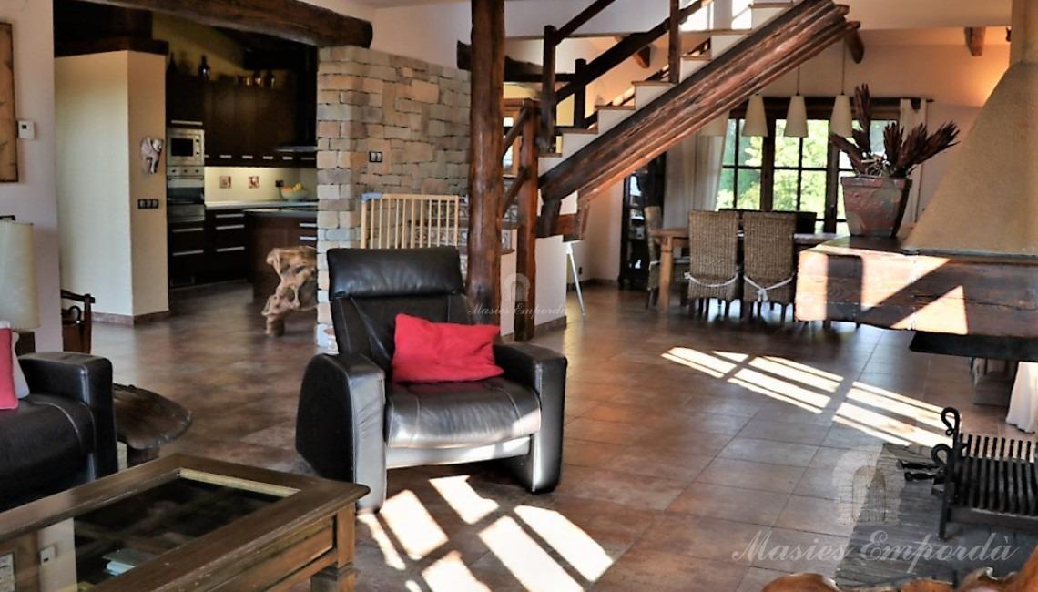 Vista del salón de estar de la casa con chimenea y el comedor al fondo de la imagen