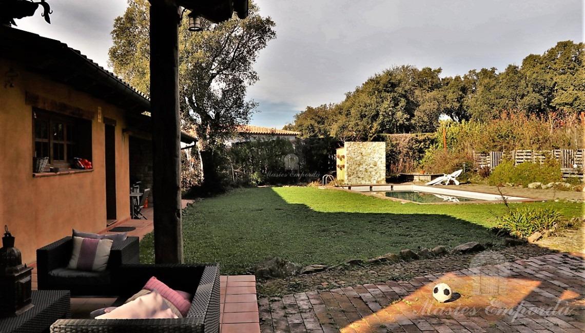Vistas del jardín y piscina desde el porche de la parte de atrás de la casa