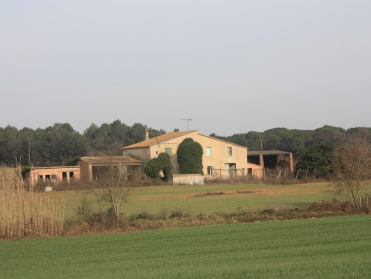 Vista del conjunto de la masía y los anexos rodeada de los campos de la propiedad