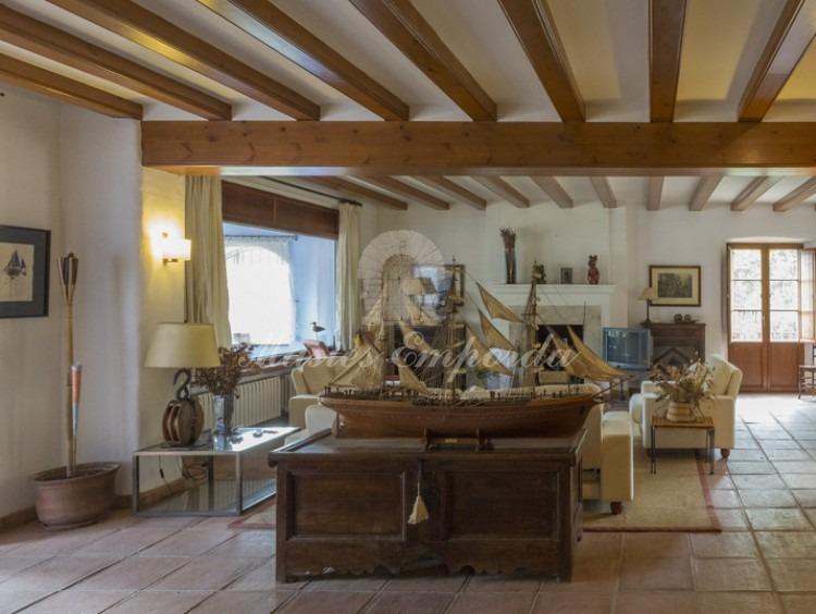 Salón principal de la casa con chimenea y cubierta con vigas de madera vistas