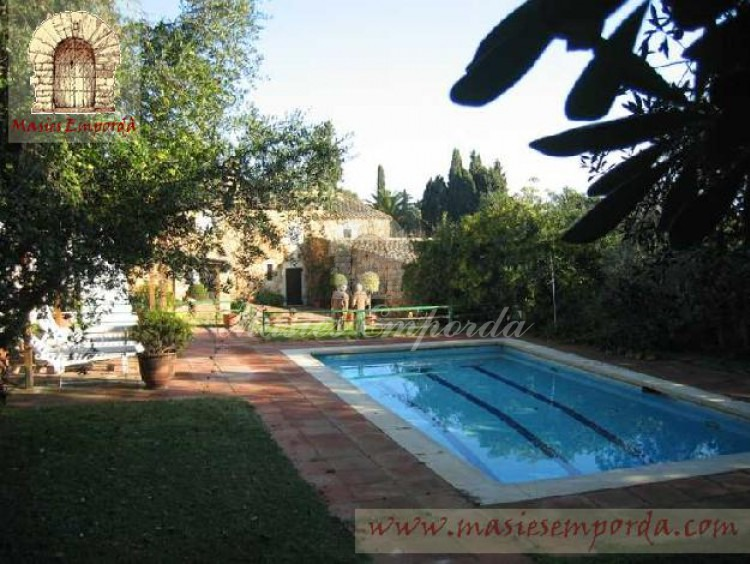 Vista de la piscina y la casa al fondo de la imagen