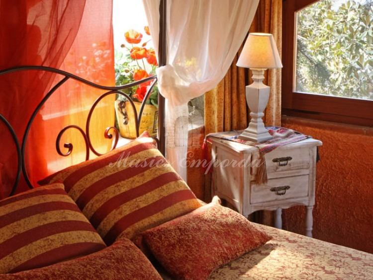 Detalles de la cama con dosel y cabezal en forja con ventanas en arco con vistas al jardín