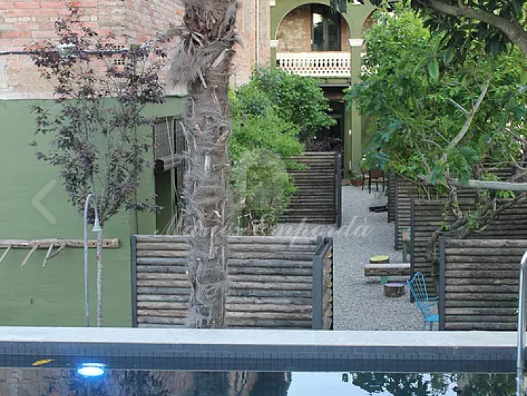 Detalle de la piscina y de la casa con parte del jardín