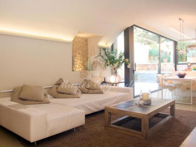 Vista del salón con un sofá de tipo cheslón en blanco y mesa de madera rectangular y al fondo vidriera que da al comedor de verano y jardín con vista de parte de la cocina de la casa