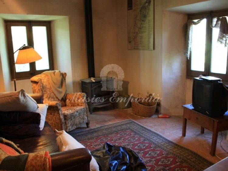 Detalle del salón de estar y biblioteca de la planta con chimenea