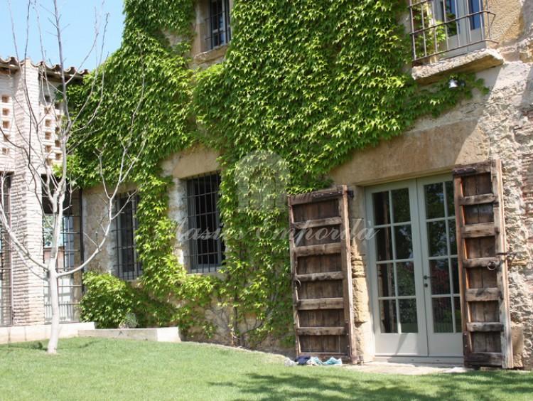 Detalle de la fachada de piedra de la casa con los portones de madera abiertos  con el pabellón de verano en un lateral de la imagen
