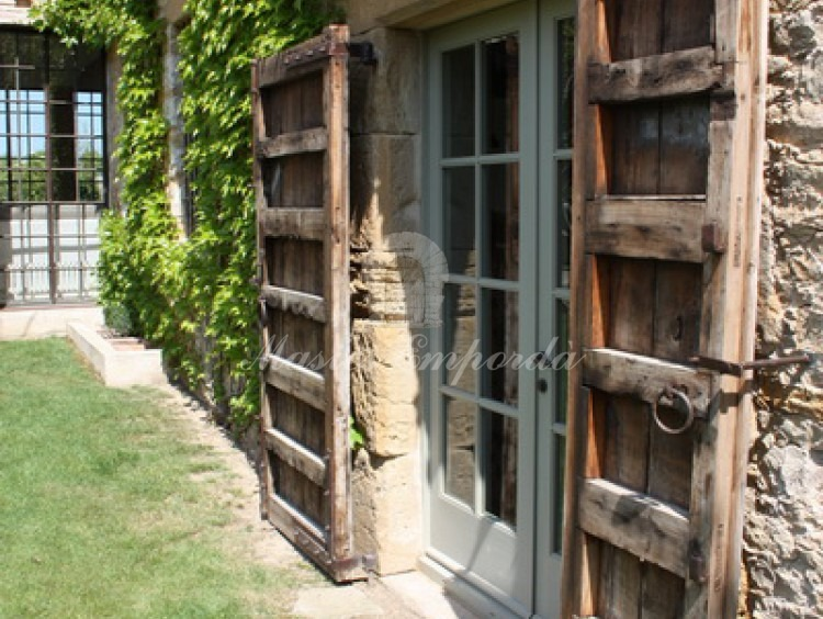 Detalle de la puerta exterior de la masía y la contra puerta en madera y acristalamiento doble