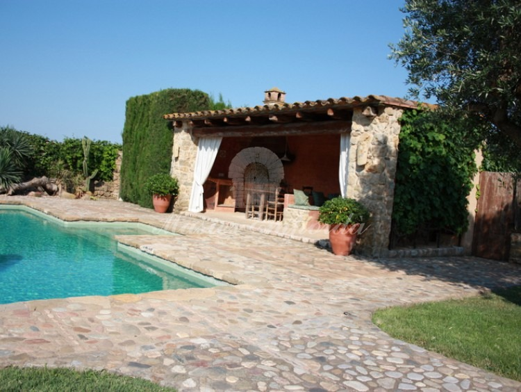 Vista de la piscina desde el jardín y del porche donde se encuentra la barbacoa