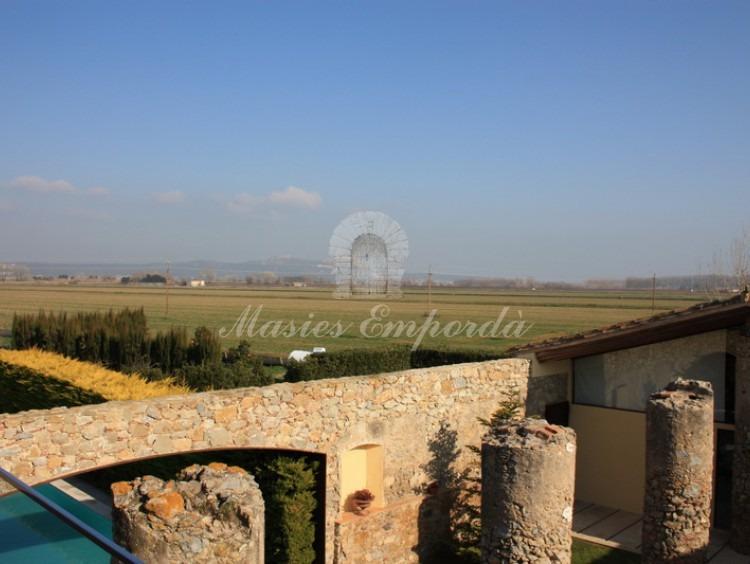 Piscina de la masía entre seto de cipreses con varios pilares testimoniales de la antigua cubierta de la casa y vista de la comarca del Baix Empordà