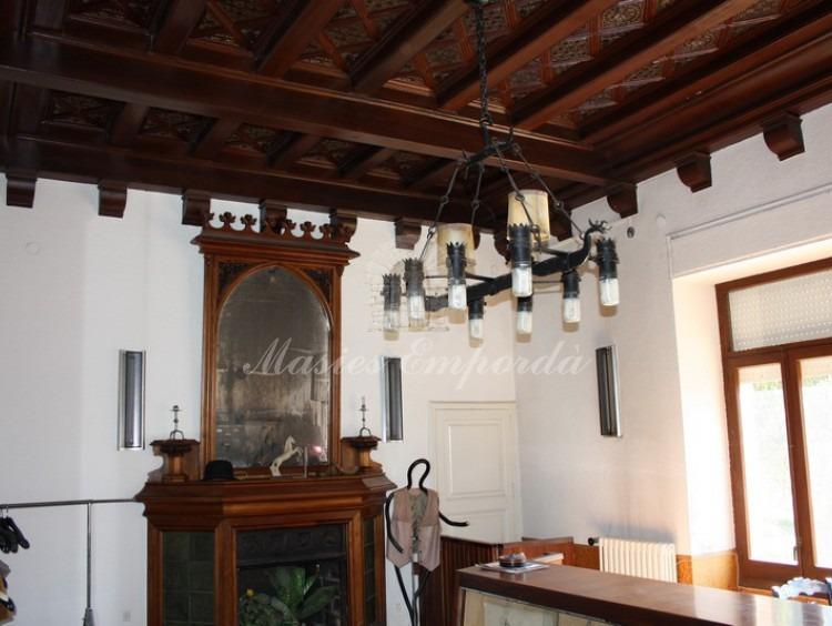 Salón de la casa con chimenea y artesonados de techo en madera con grabados y cenefas